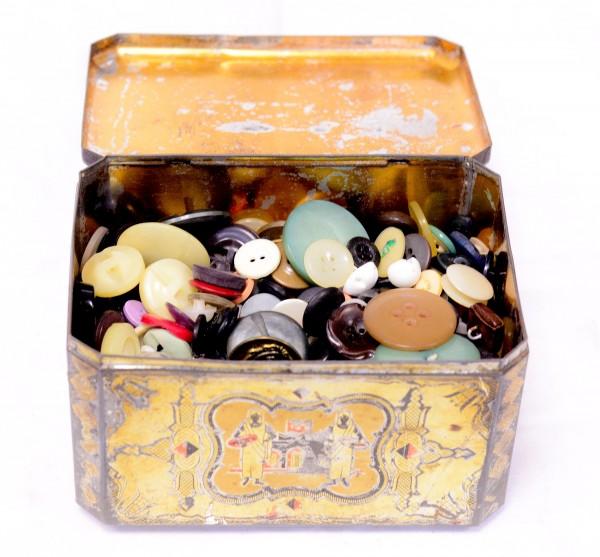 Antikes Sammelsurium an Knöpfen in alter Blechdose Fundzustand